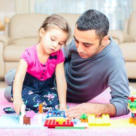 Padre e figlia giocano insieme con dei giocattoli